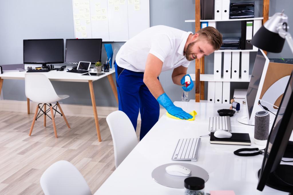 Jeune homme avec gants de ménage nettoie un bureau
