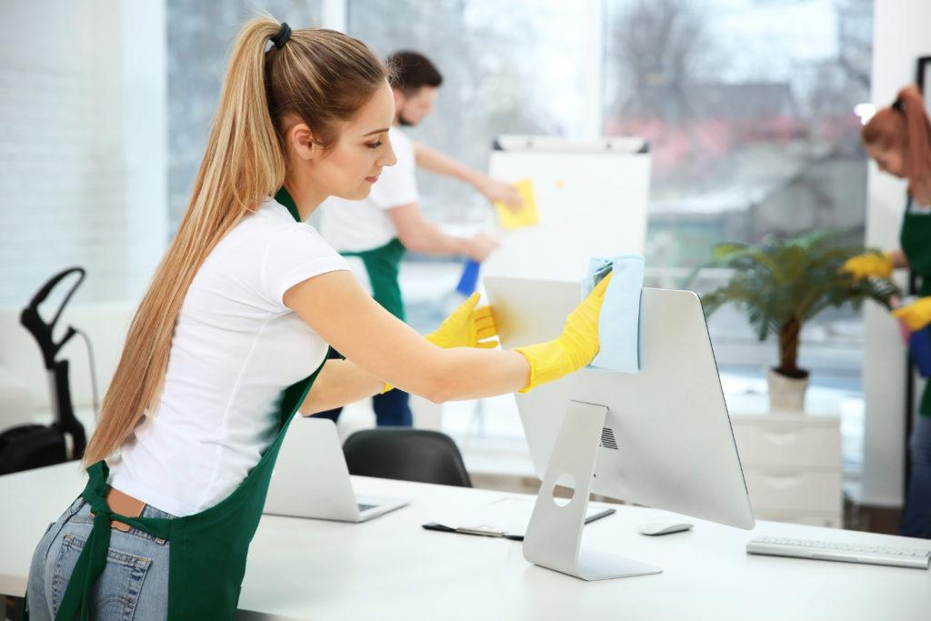 Jeune femme en gants de ménage nettoie l'écran d'un bureau